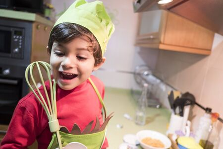 happy child 4 year old boy cooks macaroni at home with chef costume Banco de Imagens