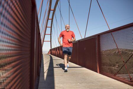 Senior runner training on a pedestrian bridge