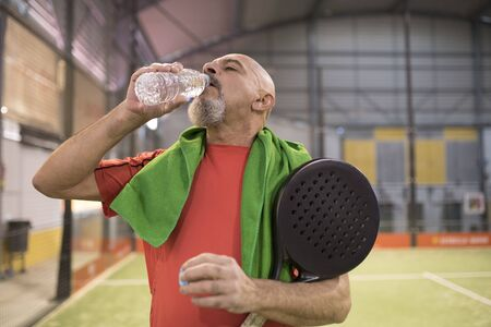 Mature man in paddle tennis court with towel and bottle of water in court Stock Photo