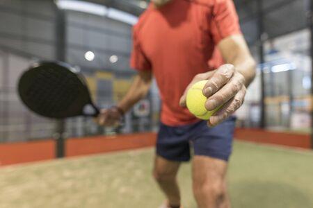 senior man playing paddle tennis at indoors pitch Reklamní fotografie