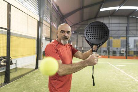 senior man playing paddle tennis at indoors pitch, backhand