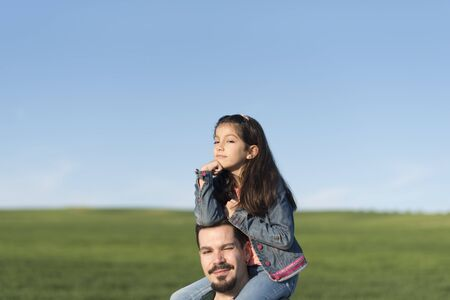 Modern father with daughter on shoulders in spring image Imagens
