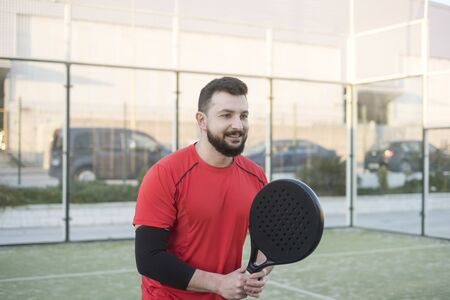 paddle tennis player in court training game with elbow warmer