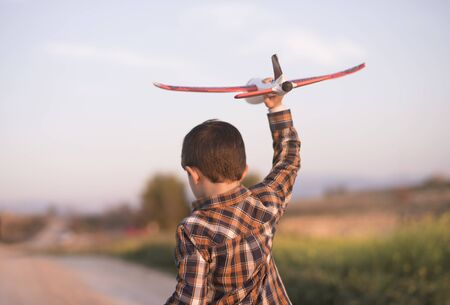 Little boy with toy airplane playing in spring outdoors image