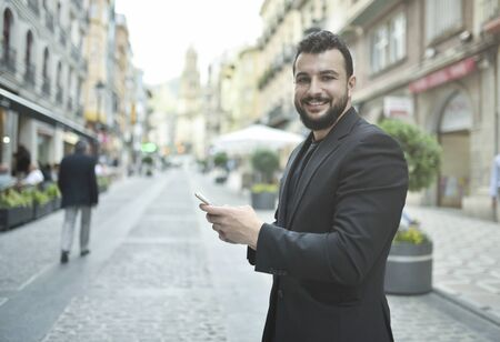 Bearded man looking phone in city outdoors 스톡 콘텐츠