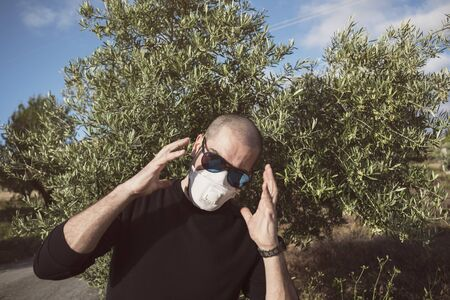 Man with sanitary mask with possible olive allergy or fear of coronavirus, focus in tree 스톡 콘텐츠