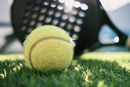 Paddle tennis racket and ball on turf still life, focus on ball