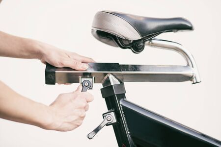 Woman adjusting spinning bike seat
