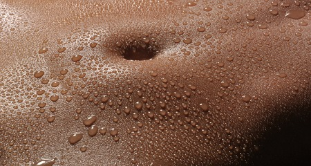 Bodyscape of a Nude woman with wet stomach and back lighting close up