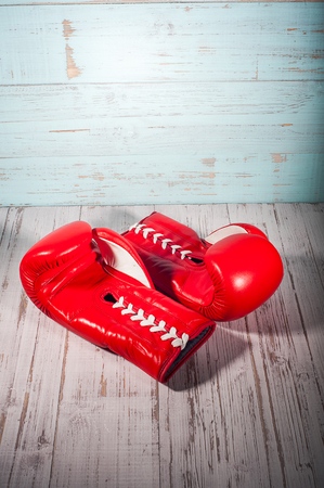Red boxing gloves on blue and white cracked wooden background, empty space Stock Photo