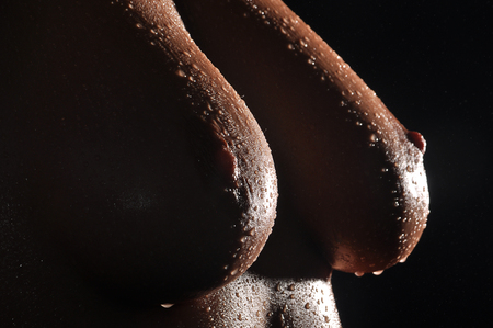 Cropped studio close up of female breasts.
