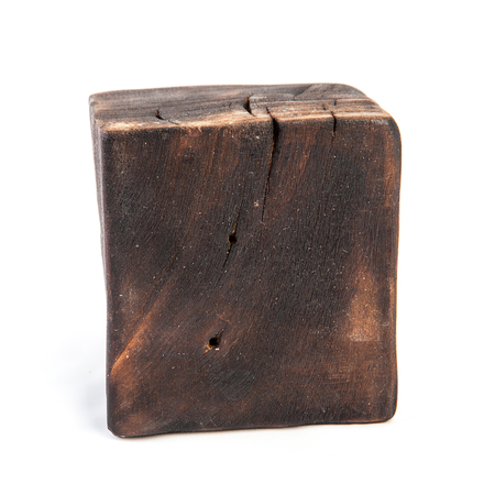 Big old dark cube is cut out from a solid trunk of an old wood. Isolated on white
