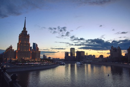 Cityscape at sunset with the colored clouds and tourboat traffic on Moskva River. Modern office buildings at the background.