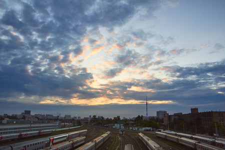 colourful lightings: Cityscape with many railway tracks and trains on them. Clouds at sunset at the background. Stock Photo