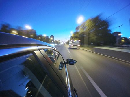 The car is moving at high speed on the night road in the city. Side camera location on the car body. Stock Photo