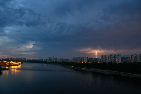 Cityscape with thunderstorm over apartments buildings and large river at foreground at dusk. Lightning bolt at background.