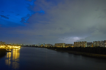 Cityscape with thunderstorm over apartments buildings and large river at foreground at dusk. Hidden lightning in the clouds at the background. Stock Photo
