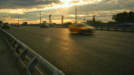 Car traffic on the bridge at sunset