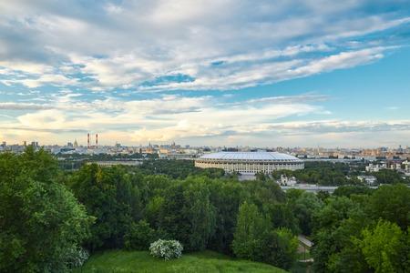 夕暮れ時にスポーツスタジアムを備えた都市景観 写真素材