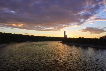 手前に川を持ち、日没時に背景に公園を持つ街並み 写真素材