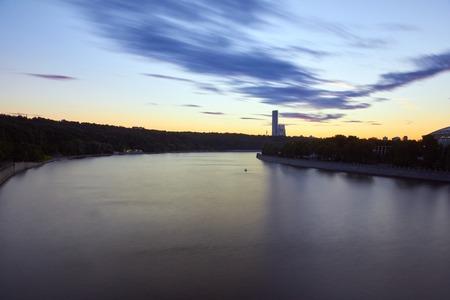 手前に川を持ち、日没時に背景に公園を持つ街並み。雲のぼやけた動き