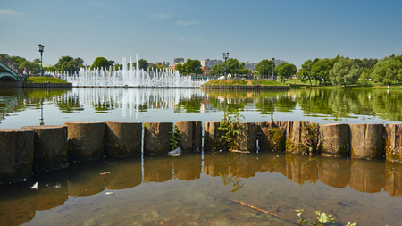 City Park on a sunny summer day. Pond in the foreground and fountain in the background