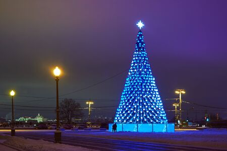 Christmas tree with lights in the foreground and artificial Northern lights in the background Фото со стока