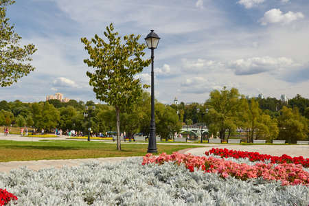 View of walking path with flower beds. West arch footbridge, Church of the Theotokos Life-giving Spring and Tsaritsyno Palace at background in Tsaritsyno Museum reserve.