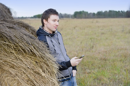 Man with a phone stands near haystack photo