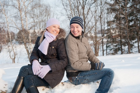 Man and woman sits on the wood at the winter background photo
