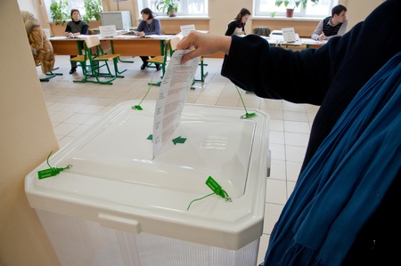 local election: MOSCOW, RUSSIA - MARCH 4: Woman put election ballot with candidates of Russian President into the box on March 4, 2012 at the local election commission in Moscow. Editorial