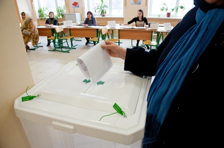 local election: MOSCOW, RUSSIA - MARCH 4: Woman put election ballot into the box on election of Russian President on March 4, 2012 in the local election commission.