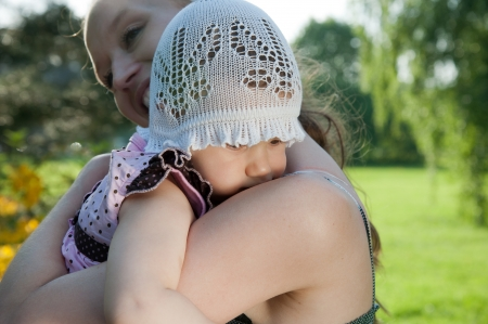 Woman holds child on shoulder in the park photo