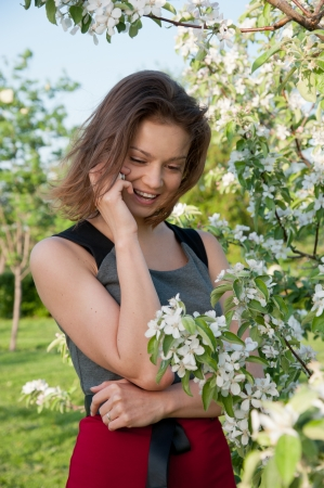 Woman talk by phone with a smile in the park near the apple tree photo