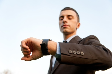 Man checking the time on the background of sky