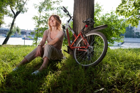 Beautiful young girl sits with a bicycle in the park photo