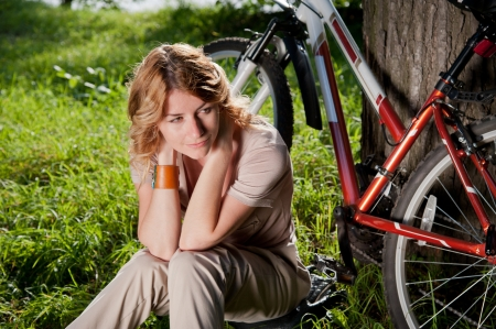 Beautiful young girl sits with a bicycle near the tree photo