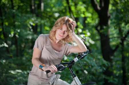 Beautiful young girl stay with a bicycle in the park photo