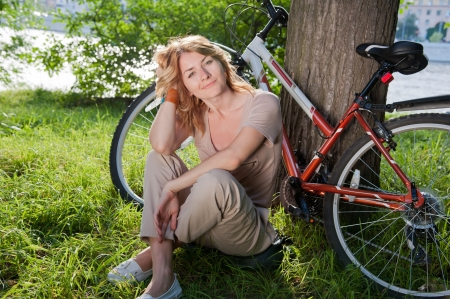 Beautiful young girl with a bicycle near the tree Standard-Bild