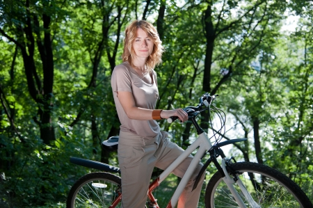 Beautiful young girl with a bicycle in the park
