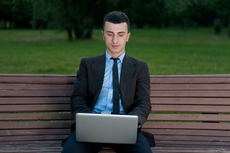 Businessman with notebook sits on the bench photo
