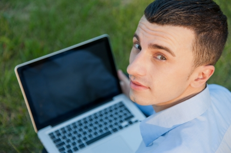 Businessman with notebook sits on the grass photo