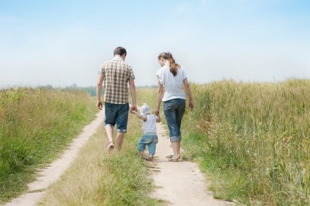 Happy family go in the meadow