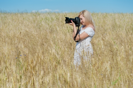 Beautiful woman take a photo with camera in the wheat field photo