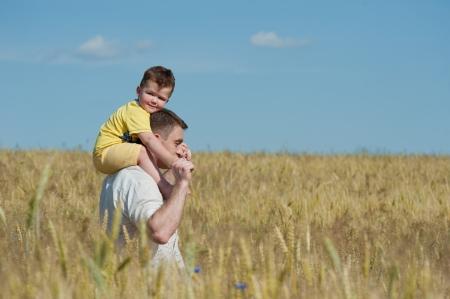 going in: Feliz padre e hijo va en el campo de trigo