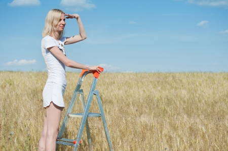 Woman stands on the stepladder and looks forward in the wheat field photo