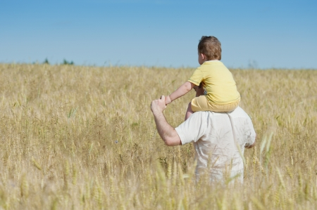 Father and son going in the wheat field photo