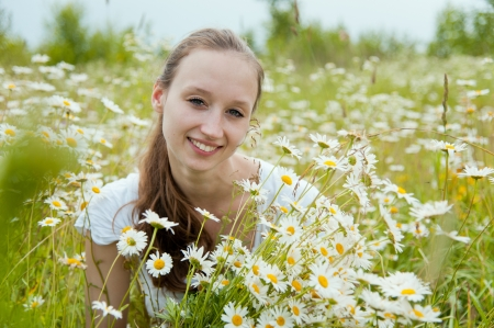 Portrait of beautiful smiling woman in the flower field photo