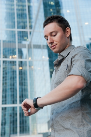 Man checking the time on the background of office buildings photo