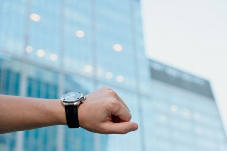 Hand with watch against office building photo